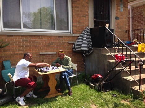 West Englewood residents playing chess in front of a house on South Damen Avenue. (Lucia Maffei/MEDILL)