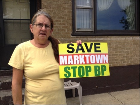 Kim Rodriguez holds up the sign she used to demonstrate against the nearby BP Oil refinery in Whiting, Indiana, as the refinery has been buying up homes in Marktown. (Cloee Cooper/Medill)